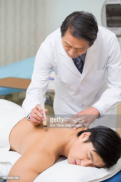 Senior doctor giving moxibustion
