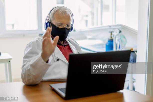 senior doctor having video conference meeting in hospital - hearing protection stock pictures, royalty-free photos & images