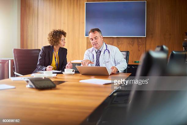 senior doctor in a business meeting - nhs staff stock pictures, royalty-free photos & images