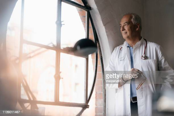 senior doctor looking out of window in medical practice - variable schärfentiefe stock-fotos und bilder