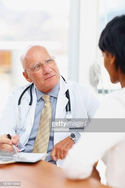 Senior médico sala de estar, con su paciente