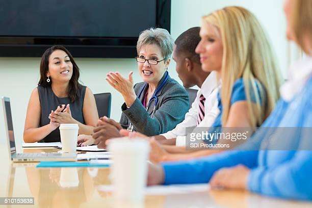 Senior parlare medico in ospedale per riunioni