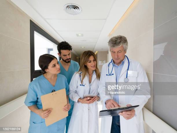 senior doctor talking to his team of interns while pointing something on clipboard at the hospital - civilian stock pictures, royalty-free photos & images