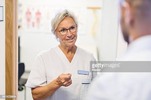 Senior doctor talking to man at orthopedic clinic