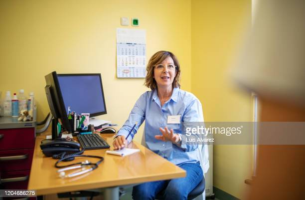senior doctor talking with her patient in clinic - shirt stock pictures, royalty-free photos & images