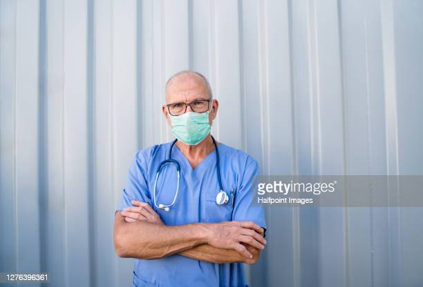 senior doctor with face mask, coronavirus and covid-19 concept. - coronavirus doctor stock pictures, royalty-free photos & images