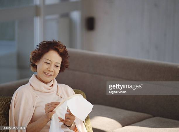 Senior embroidering in living room, smiling