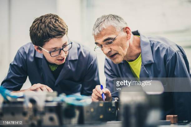 senior engineer explaining machine functioning to his student - mechanical engineering stock pictures, royalty-free photos & images