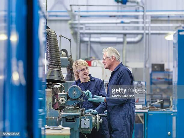 Senior engineer instructing apprentice on factory machinery