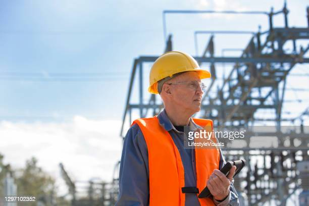 senior engineer looking and checking electric power station. - working seniors stock pictures, royalty-free photos & images