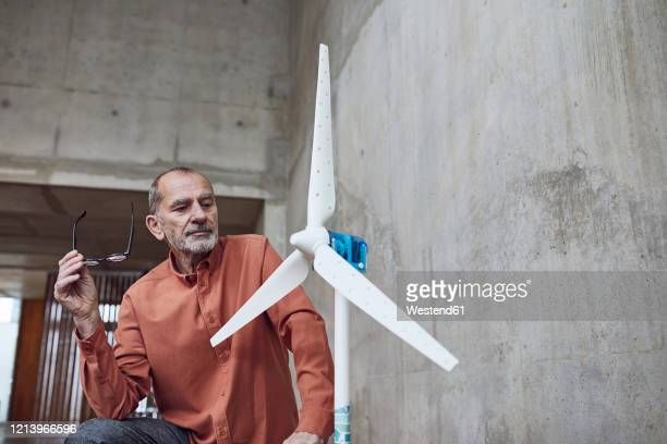 senior engineer working on wind energy solutions, looking at wind turbine - rebellion stock pictures, royalty-free photos & images