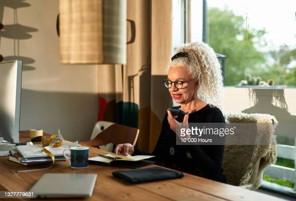 senior entrepreneur speaking on smart phone at dining table - greater london stock pictures, royalty-free photos & images