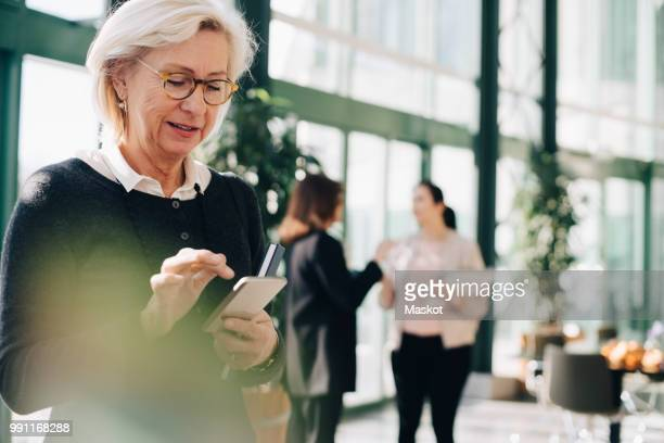 senior entrepreneur using mobile phone while coworkers discussing in background - disruptaging stock pictures, royalty-free photos & images