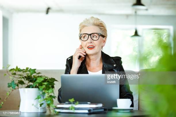 senior entrepreneur arbeitet im kreativbüro unter grünen pflanzen - izusek stock-fotos und bilder