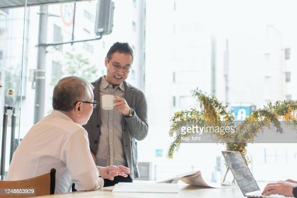 senior entrepreneurs discuss at cafe - working seniors stock pictures, royalty-free photos & images