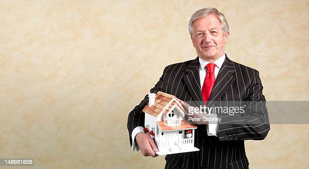 Senior estate agent with a model house