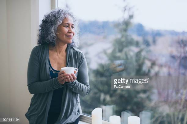 a senior ethnic woman drinks tea while contemplating the day ahead - mindfulness stock pictures, royalty-free photos & images