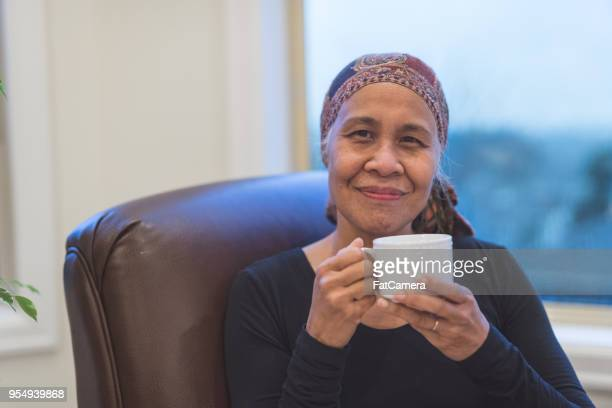 senior ethnic woman with cancer sits by her window drinking tea - cancer stock photos and pictures