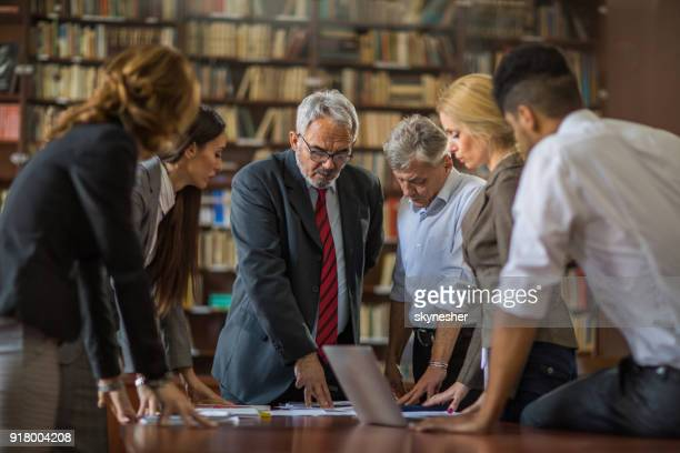 senior executive director having a meeting with his team in the office. - executive director stock pictures, royalty-free photos & images
