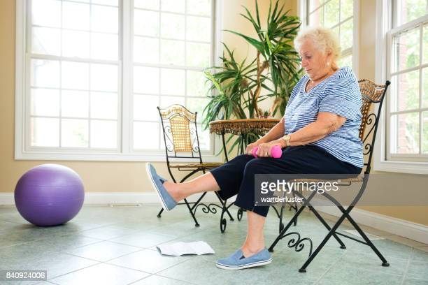 senior exercising at home - chair stock pictures, royalty-free photos & images