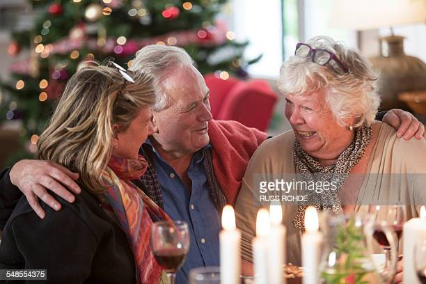 senior family laughing at christmas lunch table - tradition stock pictures, royalty-free photos & images