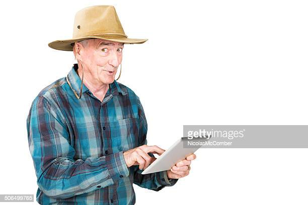 senior farmer amazed at his digital tablet - beige hat stock photos and pictures