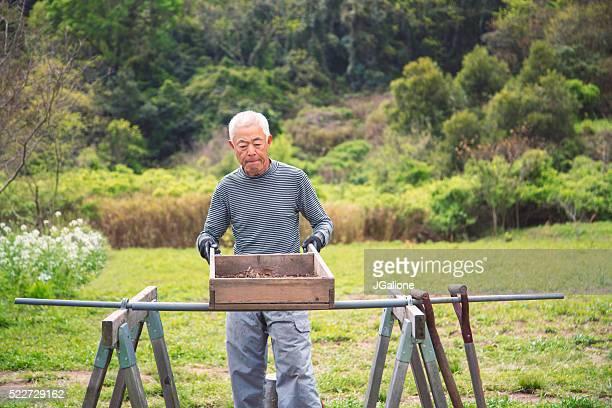Senior Landwirt Durchsieben Boden