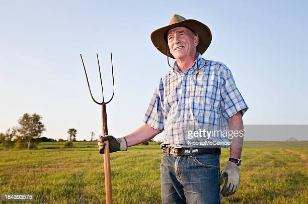 Senior farmer smiling in a field