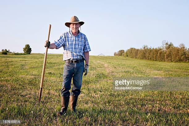 Senior farmer standing in field full length