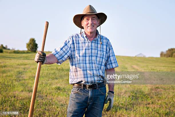 Senior farmer standing in field