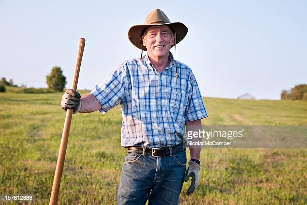 Senior agricultor de pé no campo