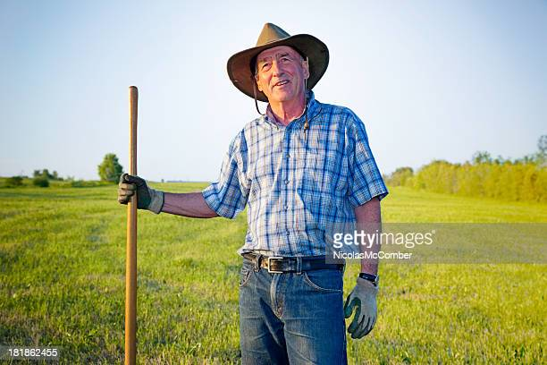 Senior farmer standing in front of field looking up
