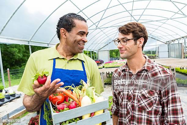 Senior farmer talks with customer at farmers' market