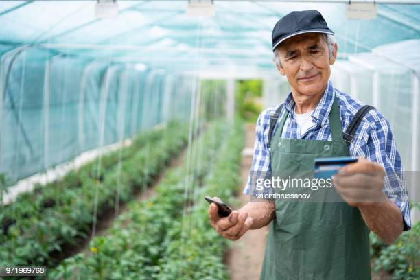 senior farmer using credit card in greenhouse - money transfer stock pictures, royalty-free photos & images
