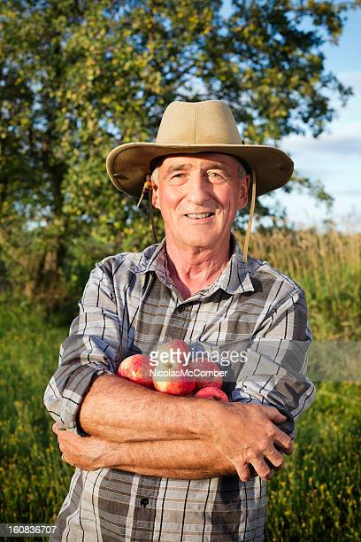 Senior farmer with organic apples in his arms