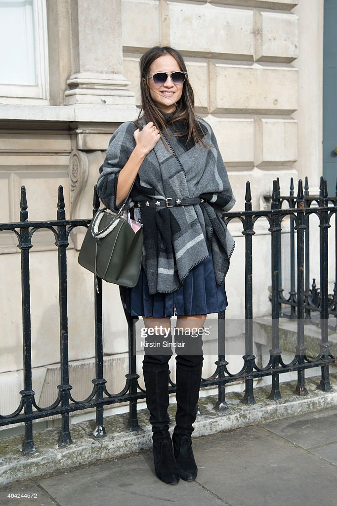 Senior Fashion Assistant at Harpers Bazaar Anna Vitiello wears Fendi bag and shirt, Dior sunglasses, Stuart Weitzman boots and a Holzweiler poncho on day 3 of London Collections: Women on February 22, 2015 in London, England.