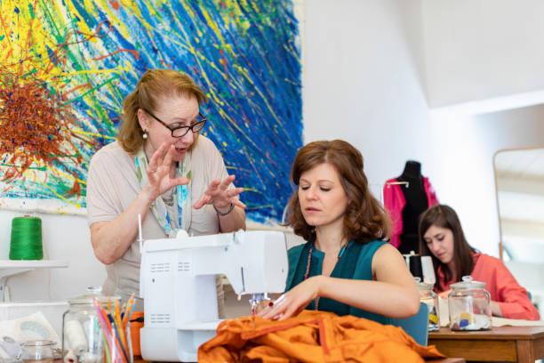 Senior fashion designer explaining seamstress about design at studio