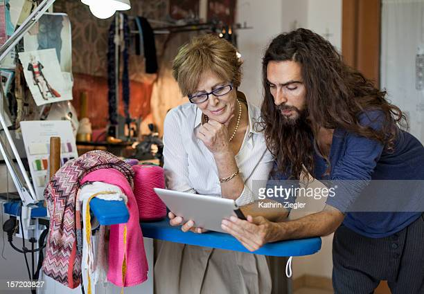 senior fashion designer in her studio with her son