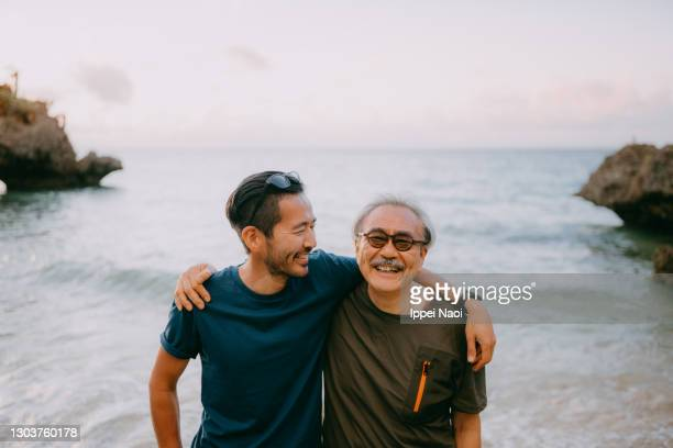senior father and adult son having a good time on beach at sunset - asia stock pictures, royalty-free photos & images