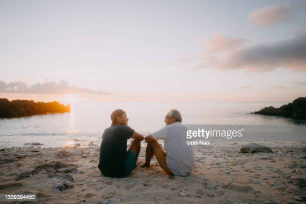 senior father and adult son having a good time on beach at sunset - tropical climate stock pictures, royalty-free photos & images