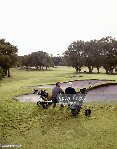 Senior father and adult son on bench at golf course, rear view