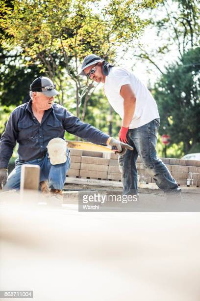 Senior father and his adult son installing paving stones