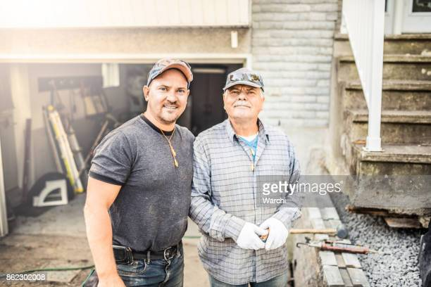 senior father and his adult son renovating their house - common stock pictures, royalty-free photos & images