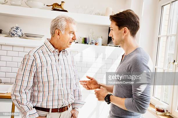 Senior father and son having a conversation in kitchen