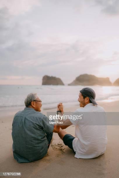 senior father and son holding hands on beach at sunset - incoraggiamento foto e immagini stock