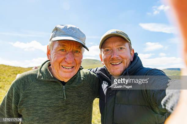 senior father and son taking a selfie whilst out hiking - senior men stock pictures, royalty-free photos & images
