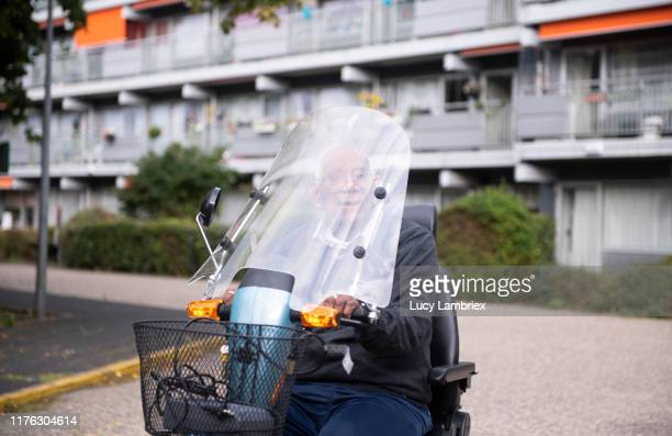 senior father riding his mobility scooter - alternative fuel vehicle stock pictures, royalty-free photos & images
