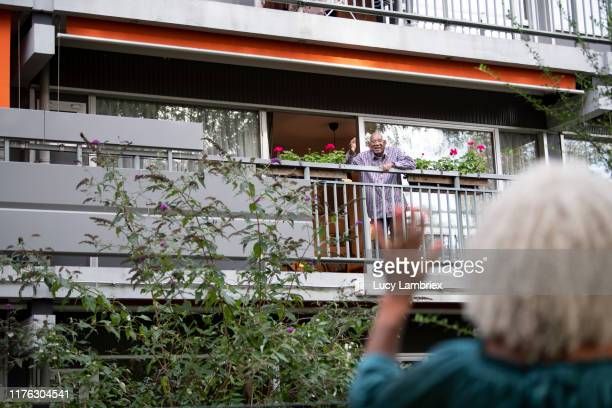 senior father waving goodbye (or hello) to his 62 year old daughter - balcony stock pictures, royalty-free photos & images