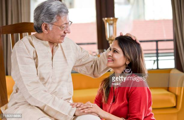 senior father with daughter at home - religious blessing stock pictures, royalty-free photos & images
