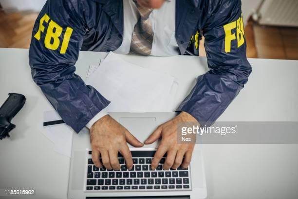 上級fbiエージェントは、オフィスでラップトップを使用しています - fbi ストックフォトと画像